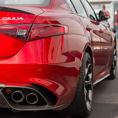 Close up rear shot of Alfa Romeo Giulia exhaust and tyres on side.