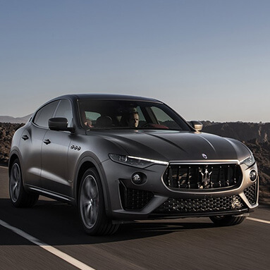 Silver Maserati Levante Vulcano being driven by a man with mountains in side view and sun shining into car.