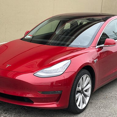 Front side view of a maroon Tesla Model 3.