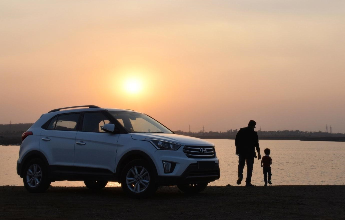White Hyundai car with the onset in the horizon and father and son holding hands.