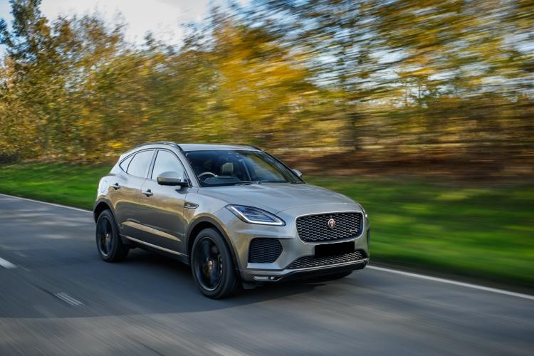 Silver Jaguar I-Pace driving on tar surrounded by forest