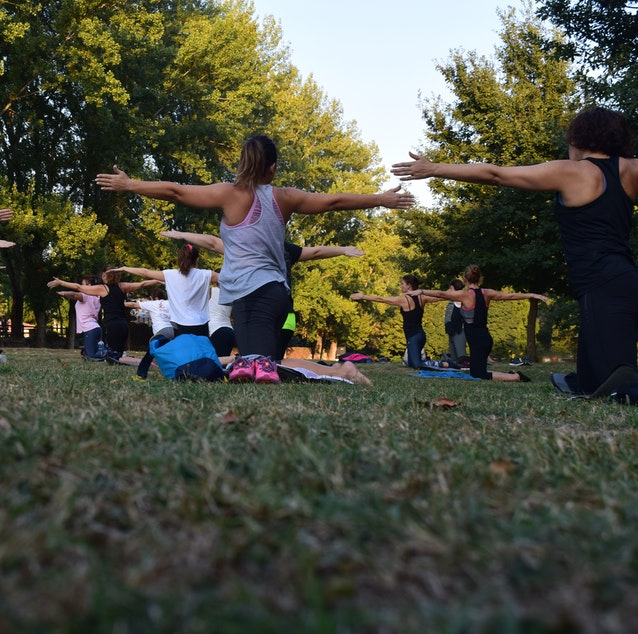 Back view of group of people doing pilates in park.
