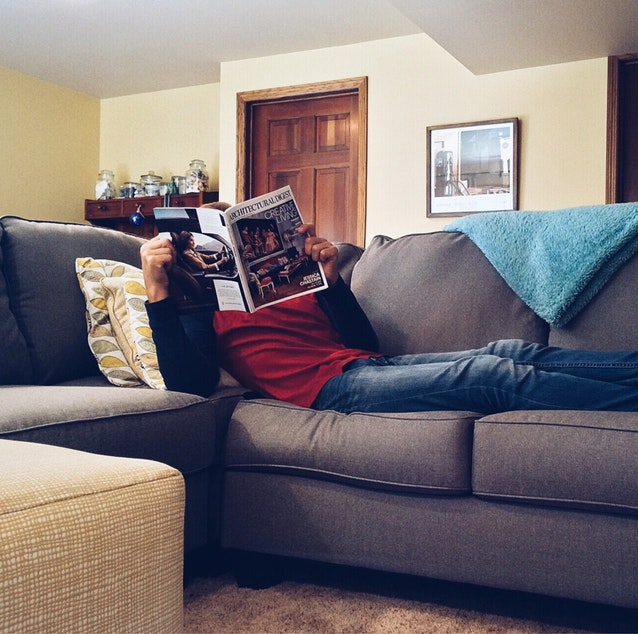 Man wearing red shirt and jeans, while reading an architecture magazine with feet up on the couch, in the living room.