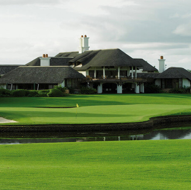 Beautiful image of Leopard Creek Golf Course , thatched-roof club house with white walls and creek in front of club house.