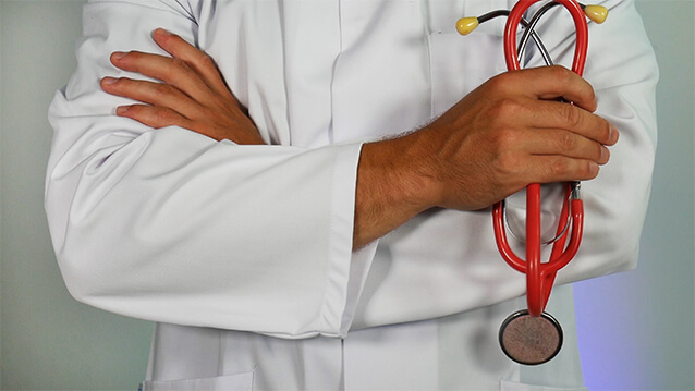 Man with white coat folding his arms holding a stethoscope