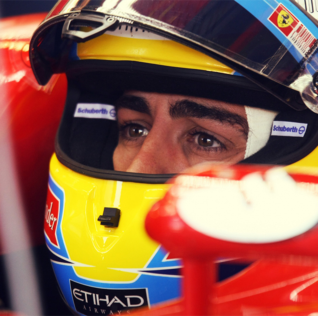 Fernando Alonso sitting in car cockpit, wearing a yellow and blue Etihad labelled helmet.