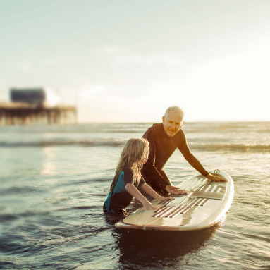 Grandfather teaching child to surf | History of our brand | Hippo.co.za partner
