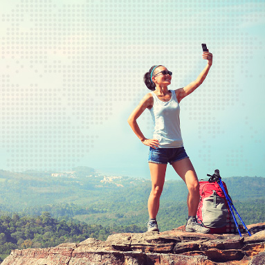 Lady standing at top of a mountain taking a selfie with the beautiful landscape in the background | Product offers | Hippo.co.za partner