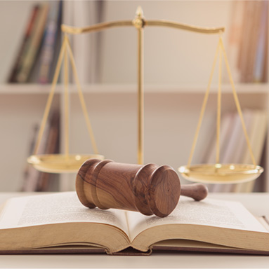 Gavel on book with weighted scale in background | History of Law for all | Hippo.co.za partner