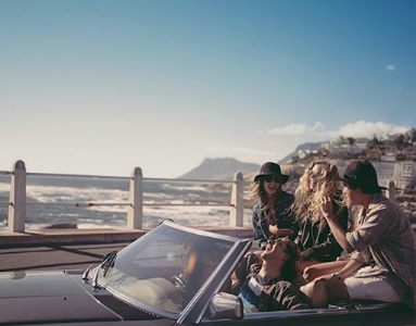 Group of friends parked in a convertible car with the sea next to them | Product offering | Hippo.co.za travel partner driving
