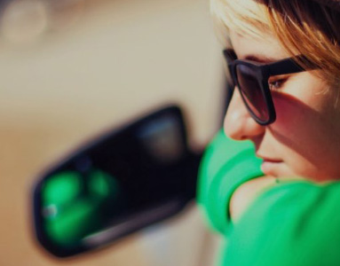 Woman leaning out of car day dreaming with sunglasses on | Unique benefits | Hippo partner