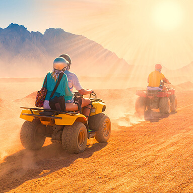 A couple, dirt biking through the desert on a sunny day with a man in front of them and dust in the air.