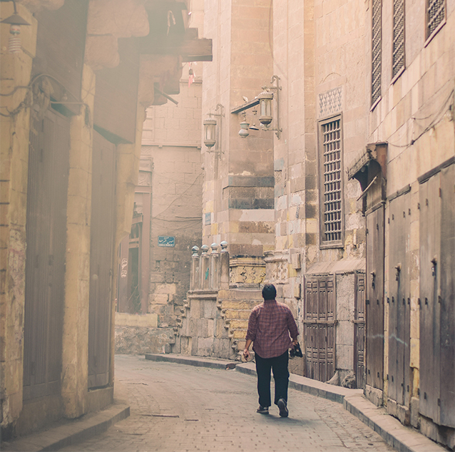 A man walking through brown high walls and apartments of Cairo City, wearing a purple shirt and holding a jacket.