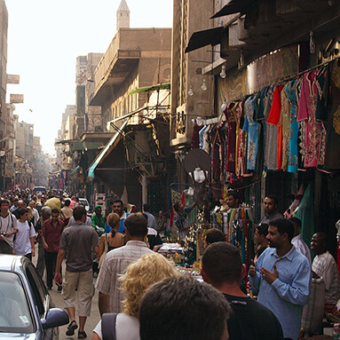 Egyptian flea market with purveyors walking past stalls and traders.