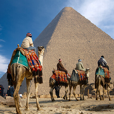 Men with colourful clothing, riding on camels in front of the pyramid.