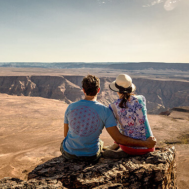 Romantic couple sitting on a cliff overlooking the Namib desert