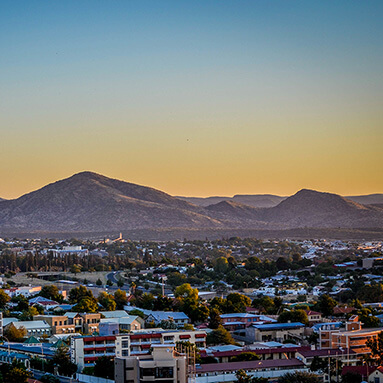 Topographical view of neat, urban Windhoek buildings, with a picturesque blue and orange sky and mountain in distance.